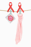 Condom hanging with red ribbon Stock Photos