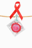 Condom hanging with red ribbon Stock Photo