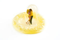 Condom with Miniatures embracing. Miniature couple embracing inside of a condom Royalty Free Stock Photography