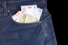 Condom, and money at jeans. On black background stock photography