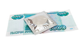 Condom with money over white Stock Image