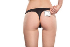 Condom near sexual ass of young beautiful woman, black thong Royalty Free Stock Images