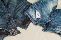A condom and a pair of jeans on the couch Stock Photos