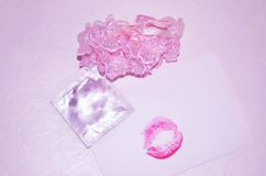 Garters, kiss and condom on white background Royalty Free Stock Photo