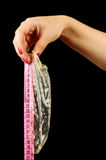 Condom and the ruler on the black background Stock Image