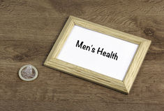 Condom on the table, wooden frame with text: Men's Health Royalty Free Stock Images