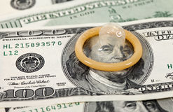 Condom and US dollars bills Royalty Free Stock Photo