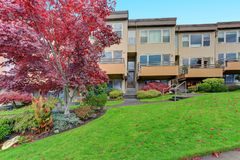 Condominium, apartment building with beige siding. Three floors, private balconies, green grass and neatly trimmed shrubs in front Royalty Free Stock Photography