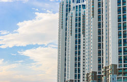 Condominium with clouds. Modern condominium with clouds and blue sky background Royalty Free Stock Photography