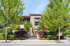 Condominium with landscaping. A view of a luxury condominium complex with beautiful landscaping in the foreground stock photo