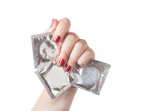 Condoms in female hand with red nails. Isolated on white background. Safe sex and love concept Stock Photo