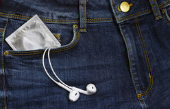 Condoms in package and headphones in jeans Royalty Free Stock Photography
