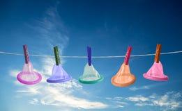 Condones que cuelgan en cuerda en fondo del cielo Imagen de archivo