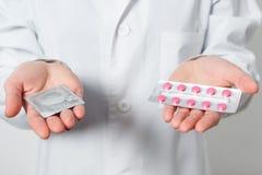 Condooms en contraceptiva in de handen van een arts voor veilig geslacht royalty-vrije stock afbeelding