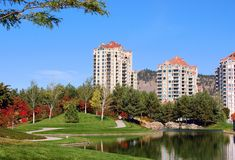 Vacation rental condos. Man-made lagoon water reflect trees on a grassy slope that fronts vacation rental condos set against a brilliant blue sky Stock Photography