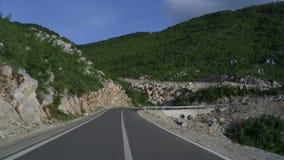 Condução através da estrada de enrolamento da montanha vídeos de arquivo