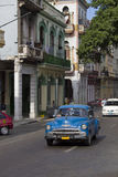 Condução de carro clássica azul abaixo da rua cubana velha Fotos de Stock Royalty Free