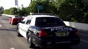 Condução de carro da polícia em arquiteturas da cidade dos EUA de uma polícia de Miami Beach da rua vídeos de arquivo