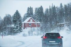 Condução de carro no blizzard com a casa vermelha no campo no inverno fotografia de stock