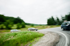 Condução de três carros em uma curvatura em uma estrada da estrada do país Fotografia de Stock
