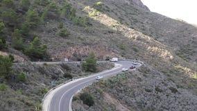 Condução de veículos lenta com cuidado em torno de um em forma de u apertado na estrada espanhola da costa através das montanhas filme