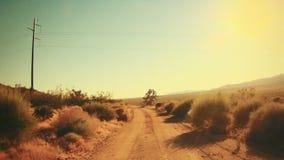 Condução em uma estrada de terra no deserto quente vídeos de arquivo