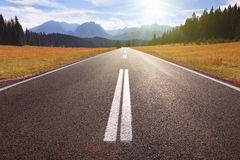 Condução em uma estrada vazia às montanhas imagens de stock