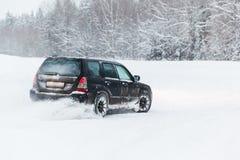 A condução extrema, o carro está movendo-se rapidamente sobre a neve lisa e cria um pulverizador da neve fotos de stock royalty free