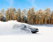 A condução extrema, o carro está movendo-se rapidamente sobre a neve lisa e cria um pulverizador da neve fotografia de stock