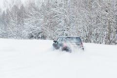A condução extrema, o carro está movendo-se rapidamente sobre a neve lisa e cria um pulverizador da neve imagem de stock