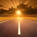 Condução na estrada asfaltada no por do sol para o sol IV Imagem de Stock
