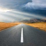 Condução na estrada asfaltada no por do sol para os raios de sol Imagem de Stock Royalty Free