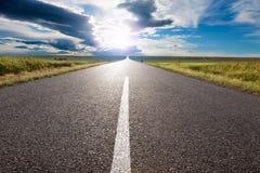 Condução na estrada vazia para o sol Foto de Stock Royalty Free