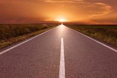 Condução na estrada vazia para o sol de ajuste Foto de Stock
