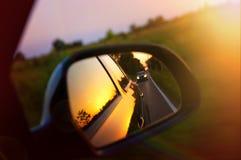 Condução no por do sol - espelho retrovisor Fotografia de Stock Royalty Free