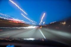 Conducción abajo de la autopista sin peaje en la noche Foto de archivo