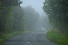 Conducción abajo de un camino brumoso de la mañana Imágenes de archivo libres de regalías