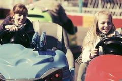Conducción adolescente feliz de las muchachas coches de parachoques Fotografía de archivo
