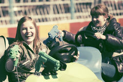 Conducción adolescente feliz de las muchachas coches de parachoques Imagen de archivo libre de regalías