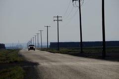 Conducción de automóviles abajo de líneas eléctricas y de postes de las linternas de la carretera nacional Foto de archivo
