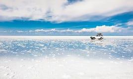 Conducción de automóviles campo a través a través de plano de la sal de Salar de Uyuni en Bolivia imagen de archivo libre de regalías