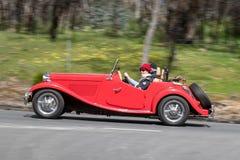 Conducción de automóviles convertible de deportes del vintage rojo en la carretera nacional imagen de archivo
