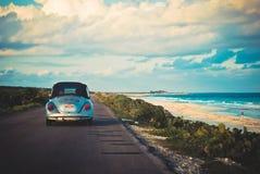 Conducción de automóviles del vintage por la playa Fotos de archivo libres de regalías