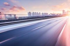 Conducción de automóviles en autopista sin peaje en la puesta del sol, falta de definición de movimiento foto de archivo libre de regalías