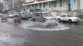 Conducción de automóviles en el camino de la calle sobre charco fangoso y salpicar el agua de las ruedas