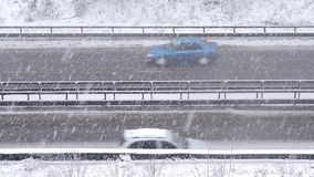 Conducción de automóviles en el camino nevoso en el invierno, tráfico en la carretera en nevadas, ventisca almacen de metraje de vídeo