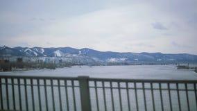 Conducción de automóviles en el puente sobre el río ancho Vista del paisaje con las montañas de la nieve Edificios traveling almacen de metraje de vídeo