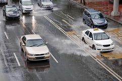 Conducción de automóviles en la calle inundada Imágenes de archivo libres de regalías