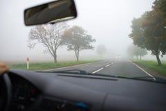 Conducción de automóviles en niebla gruesa Fotos de archivo libres de regalías