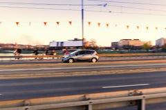 Conducción de automóviles en un camino del puente en la ciudad, en el movimiento con el fondo borroso Fotos de archivo libres de regalías